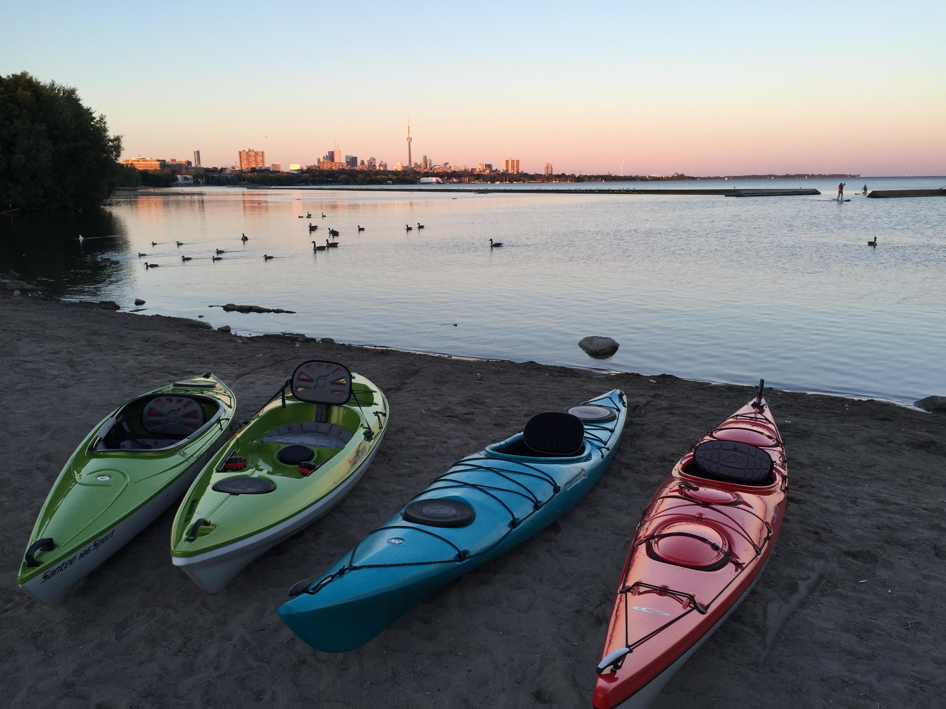 Kayaks along beach ready to paddle.